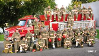 group of fire fighters in uniform in front of a firetruck