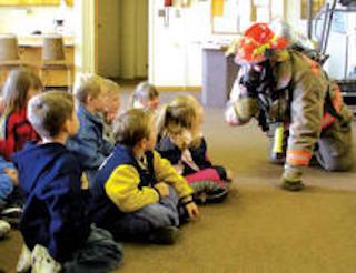 firefighter in uniform teaching a group of children